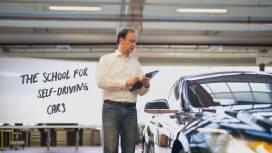 Während einer Unterrichtsstunde erklärt Dr. Oliver Pink seinen Schülern – den Autos – etwas an einer Tafel.