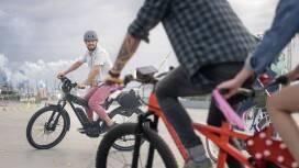 Eine Gruppe junger eBiker fahren auf dem obersten Deck eines Parkhauses durch einen Konfettiregen.