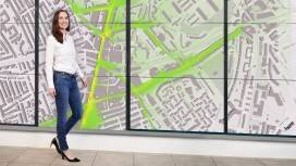 Dr. Maria Martínez Prada stands next to a wall-covering map that shows the air quality around Brixton Road.