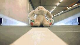 A toy bunny sits in the middle of a parking garage aisle. Headlights in the background indicate that a car is approaching.